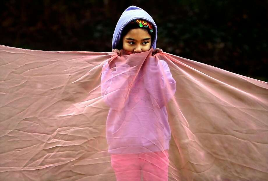 Sowing cotton with threads of lettuce?Seven-year-old Hilda Alba tries to keep warm while making a cloth garden with other kids at Dixon's Spring Art Camp in Memphis, Tenn. We have no idea what a cloth garden is. Photo: Jim Weber, Associated Press