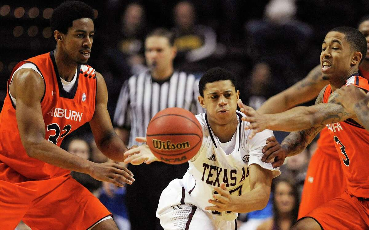 Texas A&M guard Jordan Green (13) passes the ball under pressure from Auburn forward Noel Johnson, left, and guard Chris Denson (3) during the second half of an NCAA college basketball game at the Southeastern Conference tournament, Wednesday, March 13, 2013, in Nashville, Tenn. (AP Photo/Mike Stewart)