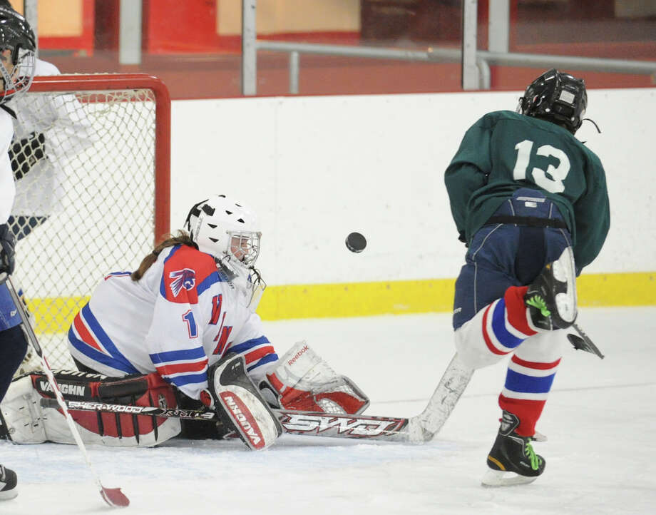 Goalie Lily Farriss of Eastern Middle School White makes a stop on Eastern Middle School Green's Connor Brust, # 13, in the Greenwich Middle School hockey challenge championship game at Hamill Rink in Byram, Wednesday, March 13, 2013. White defeated Green, 8-3. Photo: Bob Luckey / Greenwich Time