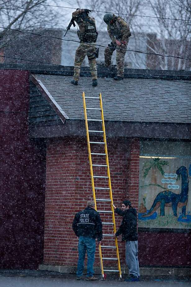 HERKIMER, NY - MARCH 13:  New York State Police officers positioned on a rooftop prepare to descend a ladder during a standoff with murder suspect Kurt Meyers on March 13, 2013 in Herkimer, New York.  Police have identified 64-year-old Kurt Meyers as a possible suspect responsible for a total of four shooting deaths and two injuries across the area earlier in the day. (Photo by Brett Carlsen/Getty Images) Photo: Brett Carlsen, Getty Images