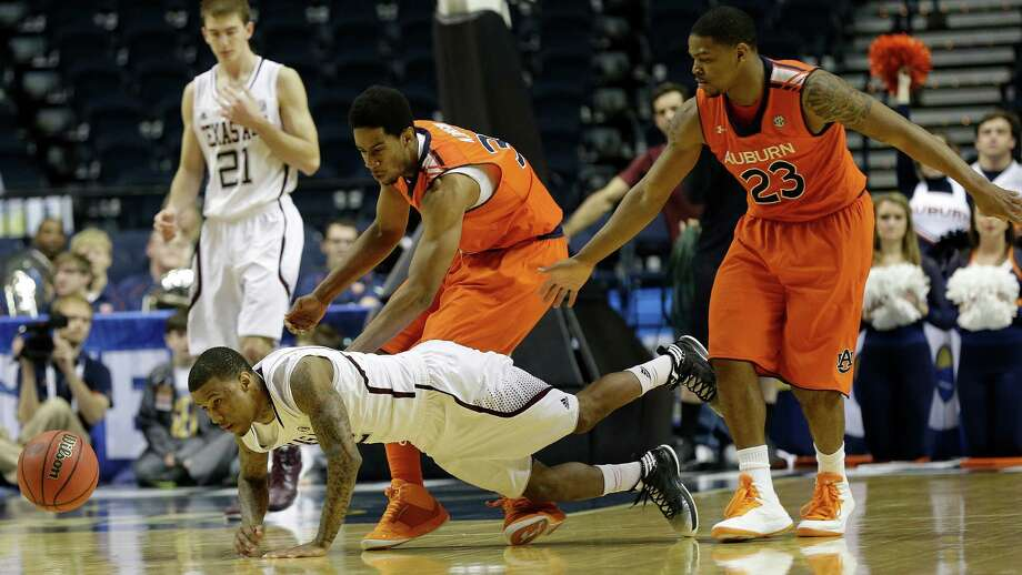 Texas A&M guard Fabyon Harris (12) vies for a loose ball as Auburn forward Noel Johnson (32) and Auburn guard Frankie Sullivan (23) defend during the second half of an NCAA college basketball game at the Southeastern Conference tournament, Thursday, March 14, 2013, in Nashville, Tenn. Texas A&M won 71-62. (AP Photo/Dave Martin) Photo: Dave Martin, Associated Press / AP