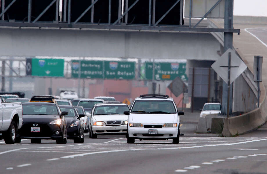 A commuter drives very slow on the shoulder attempting to time his arrival at the Bay Bridge toll plaza for precisely 10 a.m. to avoid paying a $6 toll in Oakland, Calif. on Tuesday, March 12, 2013. Some drivers will wait on the shoulder before the pay gates until the tolls drop to $4 after 10 a.m. Photo: Paul Chinn, The Chronicle / ONLINE_YES