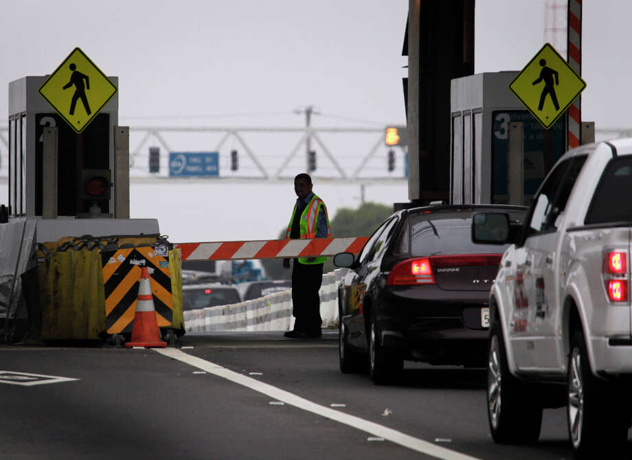 A toll taker prepares to open the carpool line for regular traffic after the toll drops from $6 to $4 after 10 a.m. at the Bay Bridge toll plaza in Oakland, Calif. on Tuesday, March 12, 2013. Some drivers will pull over on the shoulder before the pay gates and wait until 10 a.m. to avoid paying the extra $2. Photo: Paul Chinn, The Chronicle / ONLINE_YES