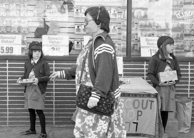 March 29, 1988: Girl Scouts sell cookies outside the Walgreen's on Clement in San Francisco. A strolling smoker absorbed in her Walkman cassette (I'm guessing Yanni's 'Keys to Imagination') walks by, oblivious to their Trefoils and adorable bangs. It's hard to be a Scout in The City. Photo: Deanne Fitzmaurice, The Chronicle / ONLINE_YES