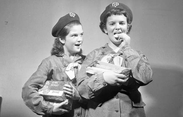 March 10, 1956: Martha Phillips and Evelyn Vattuone eat the product during an early Girl Scouts cookie sale. They sold vanilla and vanilla/chocolate cookies, which sold for 35 and 40 cents. The coats are frumpy, but the head wear has a rakish (then 8-year-old) Samuel L. Jackson vibe. Photo: Art Frisch, The Chronicle / ONLINE_YES