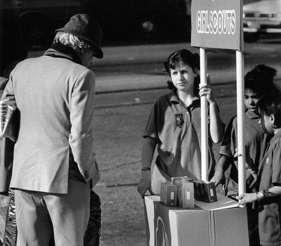 March 18, 1988: Stephanie Schroeder sells cookies in San Francisco. She looks somewhat disinterested in this photo. But by the 1980s, Girl Scout cookies were becoming a buyer's market. That's how addiction works. This guy's probably spending his last $2.50 on some Thin Mints. Photo: Frederic Larson, The Chronicle / ONLINE_YES