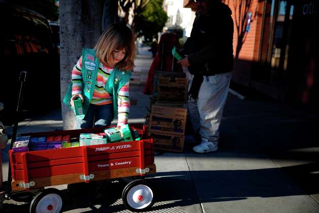 Feb. 14, 2013: Maggie Brown, 9, of San Francisco sells Girl Scout cookies on the corner of Chestnut and Pierce Streets in San Francisco. The red wagon is a nice Norman Rockwell touch. Note the casual clothing and lack of a sash.  (I'm not a Girl Scout vest fan. Reminds me of Target.) Photo: Lea Suzuki, The Chronicle / ONLINE_YES