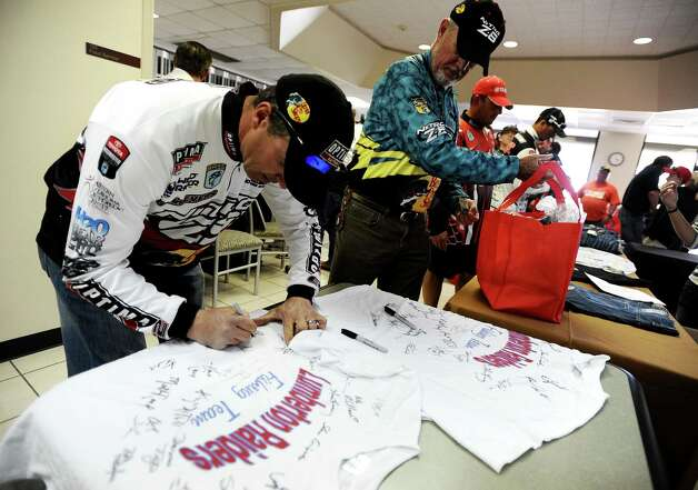 Angler Edwin Evers signs a shirt set up for the Lumberton High School fishing team before a short briefing at Lamar Orange for the B.A.S.S. Bassmasters 2013 Elite Series Sabine River Challenge which begins on Thursday, March 14, 2013 at the City of Orange Boat Dock. Photo taken: Randy Edwards/The Enterprise Photo: Randy Edwards