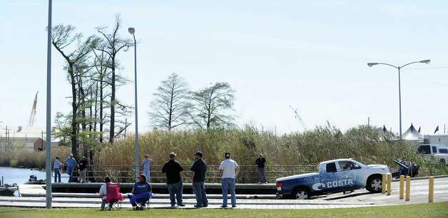 Spectators watch as anglers begin to head to the dock after some practice for the B.A.S.S. Bassmasters 2013 Elite Series Sabine River Challenge which begins on Thursday, March 14, 2013 at the City of Orange Boat Dock. Photo taken: Randy Edwards/The Enterprise Photo: Randy Edwards