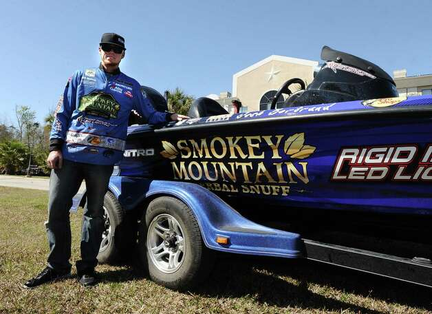 Arizona angler Josh Bertrand stands next to his boat that is charging behind the Holiday Day Inn Express on Interstate 10 in Orange in preparation for the B.A.S.S. Bassmasters 2013 Elite Series Sabine River Challenge which begins on Thursday, March 14, 2013 at the City of Orange Boat Dock. Photo taken: Randy Edwards/The Enterprise Photo: Randy Edwards