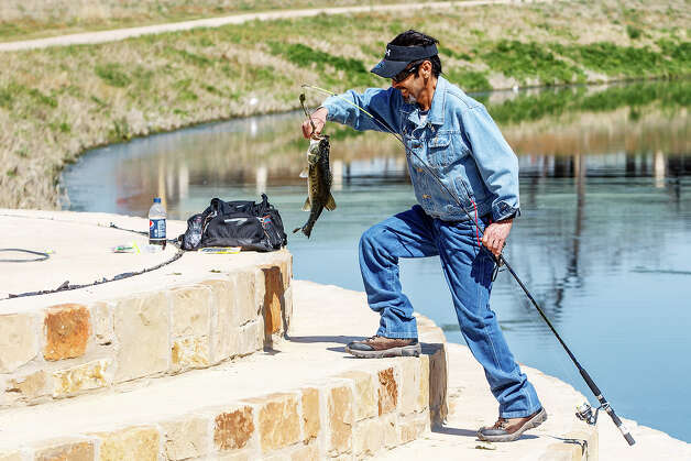 Thomas Benitez catches a Largemouth Bass on a plastic worm while enjoying the day at Padre County Park on the Mission Reach on Wednesday, March 13, 2013.  MARVIN PFEIFFER/ mpfeiffer@express-news.net Photo: MARVIN PFEIFFER, Marvin Pfeiffer/ Express-News / Express-News 2013