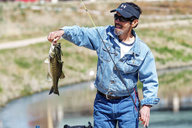 Thomas Benitez shows off a Largemouth Bass he caught on a plastic worm while enjoying the day at Padre County Park on the Mission Reach on Wednesday, March 13, 2013.  MARVIN PFEIFFER/ mpfeiffer@express-news.net Photo: MARVIN PFEIFFER, Marvin Pfeiffer/ Express-News / Express-News 2013