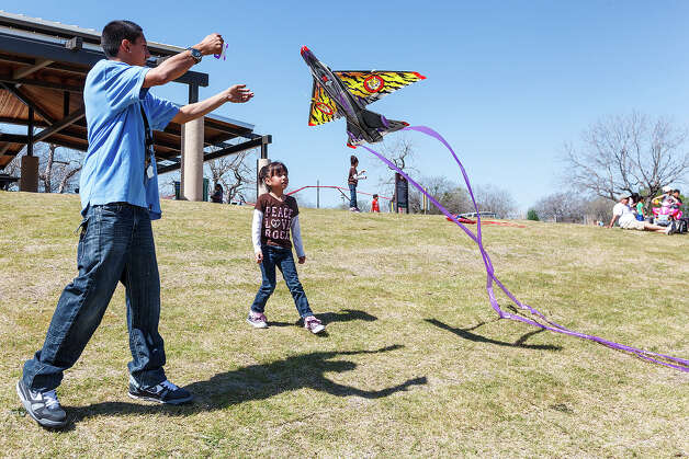 Guillermo Cantu helps five-year-old Jaylen Hernandez get her kite into the air a they and others enjoyed the day at Padre County Park on the Mission Reach on Wednesday, March 13, 2013.  MARVIN PFEIFFER/ mpfeiffer@express-news.net Photo: MARVIN PFEIFFER, Marvin Pfeiffer/ Express-News / Express-News 2013