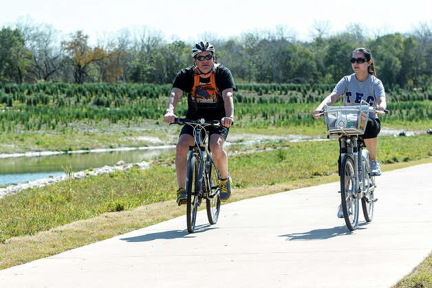Chris Dortch (left) and Jennifer Papayanopolus ride their bikes down Mission Reach in Padre County Park on Wednesday, March 13, 2013.  MARVIN PFEIFFER/ mpfeiffer@express-news.net Photo: MARVIN PFEIFFER, Marvin Pfeiffer/ Express-News / Express-News 2013