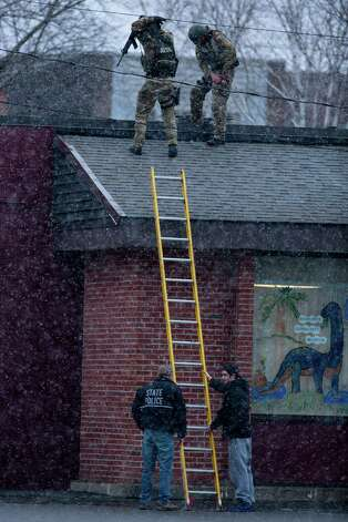 HERKIMER, NY - MARCH 13:  New York State Police officers positioned on a rooftop prepare to descend a ladder during a standoff with murder suspect Kurt Meyers on March 13, 2013 in Herkimer, New York.  Police have identified 64-year-old Kurt Meyers as a possible suspect responsible for a total of four shooting deaths and two injuries across the area earlier in the day. Photo: Brett Carlsen, Getty Images / 2013 Getty Images