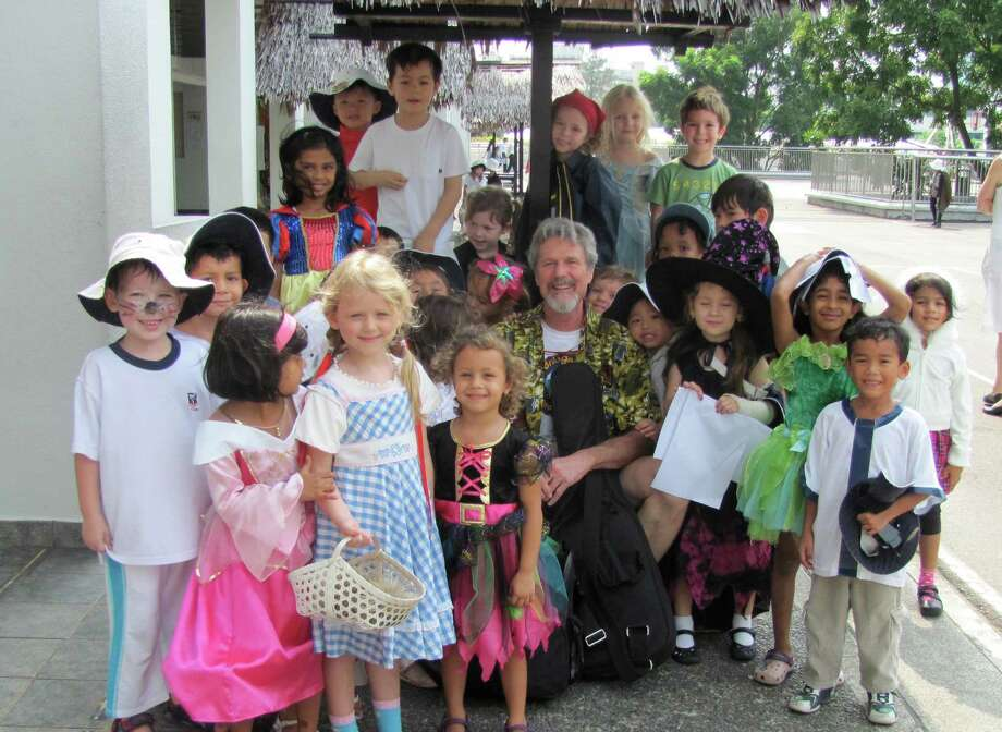 "Singer-songwriter and humanitarian John Farrell, center, is seen here with some children he got to know in Singapore. It was during that trip that he wrote ""It's the Little Things,"" a beautiful tune that's one among the many he will share at ""Joining Hands & Voices,"" a benefit sing-along at the Palace Danbury on Saturday, March 16. Photo: Contributed Photo"