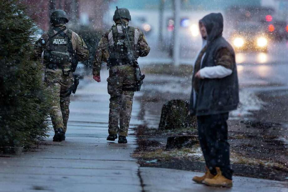 HERKIMER, NY - MARCH 13:  Members of the New York State Police walk past a citizen after switching off with another team for a rooftop position during a standoff with murder suspect Kurt Meyers on March 13, 2013 in Herkimer, New York.  Police have identified 64-year-old Kurt Meyers as a possible suspect responsible for a total of four shooting deaths and two injuries across the area earlier in the day. Photo: Brett Carlsen, Getty Images / 2013 Getty Images