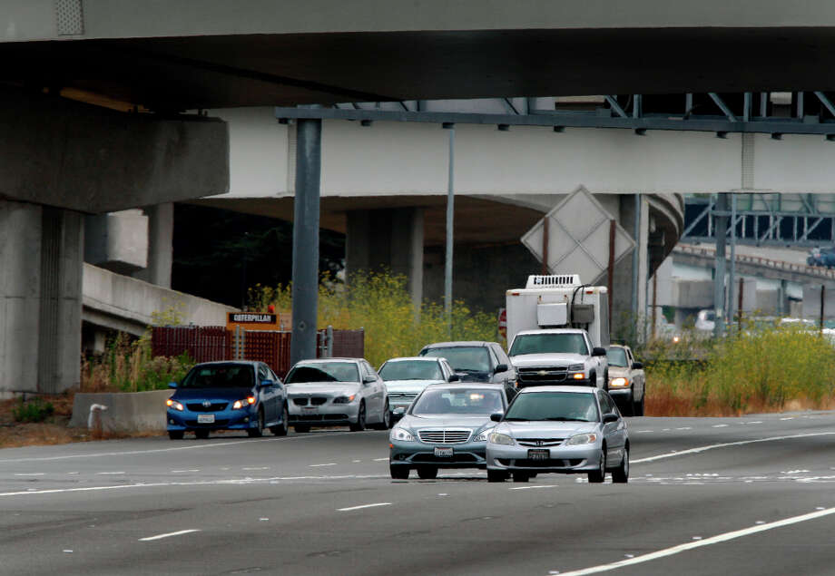 Commuters wait on the shoulder east of the Bay Bridge toll plaza for the toll to drop to $4 at 10 a.m. in Oakland, Calif., on Wednesday, July  28, 2010. The Bay Area Toll Authority implemented a weekday congestion pricing toll system which charges $6 to cross the Bay Bridge at peak commute times and then drops to $4 during midday. Photo: Paul Chinn, The Chronicle / SFC