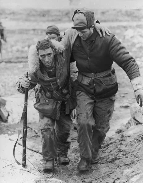 1950:  A United Nations soldier in uniform helps a wounded Canadian rifleman to an aid station behin
