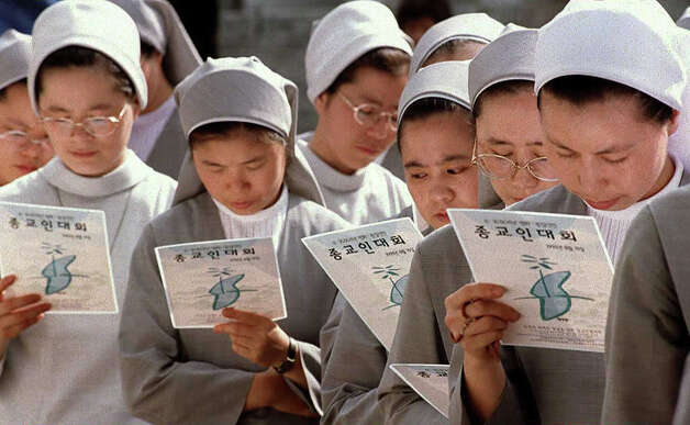 South Korean Catholic nuns pray for unification of communist North Korea and capitalist South Korea at Chogye Buddhist Temple 12 August in Seoul.  Monks, nuns and Protestants later walked together to Myongdong Catholic Cathedral. The prayer cards show a map of Korea with no demilitarized zone. Photo: Str-cho SUNG-SU, AFP/Getty Images / AFP