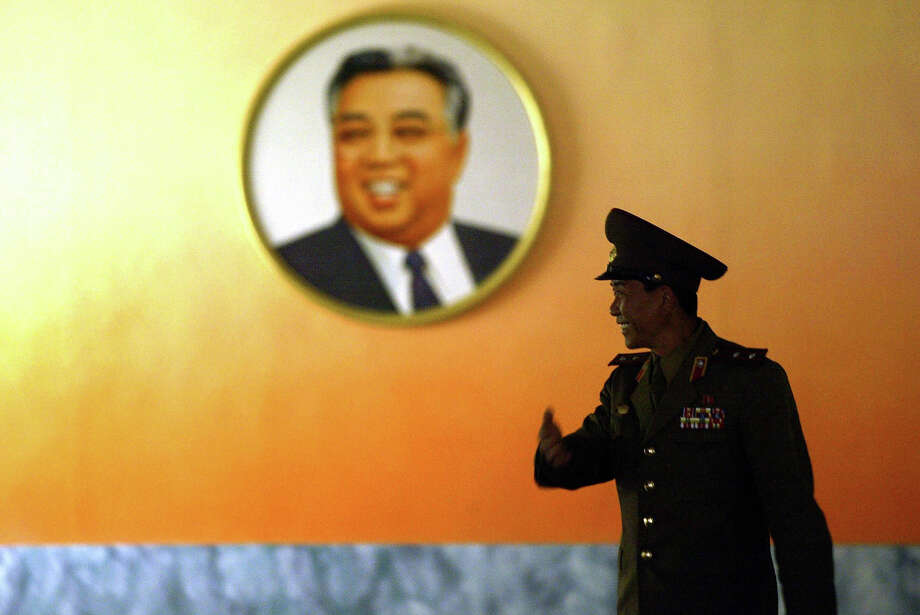 Lt. Col. Sung Jong-Chol of the North Korean army guides visitors in front of a picture of the late leader Kim Il-Sung on the North's side of the Demilitarized Zone (DMZ) at Panmunjom, 27 March 2005. The division of the Korean peninsula between the communist north and the capitalist south led to the 1950-53 Korean War with the two sides still technically at war ever since an armistice was signed in 1953 dividing the two Koreas. Photo: PETER PARKS, AFP/Getty Images / 2005 AFP