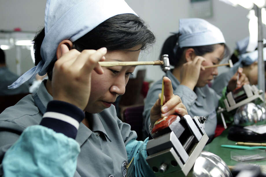 North Korean women work at the assembly line of the factory of South Korean Watch company Romanson at the Kaesong industrial complex on May 22, 2007 in Kaesong, North Korea. 300 South Korean companies, mostly labour-intensive manufacturers, are waiting to build their factories on the site by the end of 2007, just 10 km north of the world's most heavily fortified border bisecting the two Koreas. They plan to hire more than 100,000 North Koreans to make products ranging from shoes and watches, clothes, according to officials from Kaesong industrial complex. About 2,000 South Korean companies have applied to move their production facilities into the Kaesong complex, where they can pay only one-thirtieth of the monthly wage per worker they pay at home or half the pay even in China. Photo: Chung Sung-Jun, Getty Images / 2007 Getty Images