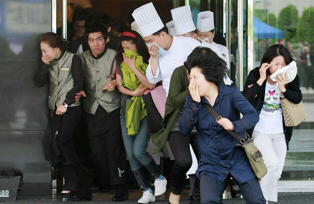 South Koreans rush out into the street during a drill against possible threats from North Korea at the Marriott hotel on May 28, 2010 in Seoul, South Korea. The exercise is intended to prepare the South Korean defense force for any potential action from North Korea and preparation for possible terrorist attacks during the upcoming G-20 Finance Minister and Central Bank Governors Meeting to be held in Busan in June, this year. Photo: Chung Sung-Jun, Getty Images / 2010 Getty Images