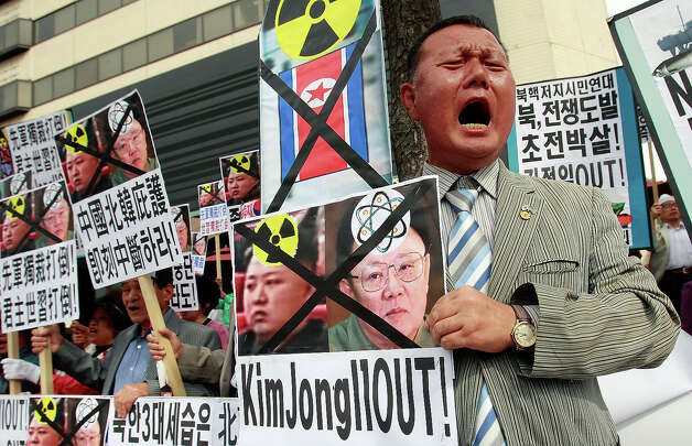 South Korean protestors hold portraits of North Korean leader Kim Jong-Il and his son Kim Jong-Un and shout slogans at a rally opposing recent political decsions made by North Korea's  ruling party on October 1, 2010 in Seoul, South Korea.  The protest comes amidst fresh talks between the the two Koreas aimed at reuniting families seperated during conflict 60 years ago. North Korean leader Kim has recently been re-appointed as the party's secretary general and has made a military general of Kim Jong-Un, believed to be his third son. Photo: Chung Sung-Jun, Getty Images / 2010 Getty Images
