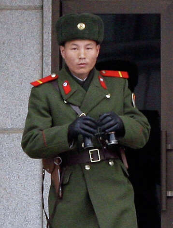 A North Korean soldier stands guard as the border town reopens following North Korea's attack on Yeonpyeong in late November, on December 8, 2010 in Panmunjom, South Korea. Dozens of artillery shells fired by North Korea struck the South Korean Island of Yeonpyeong on November 23, resulting in four deaths and further injuries, prompting return fire from South Korean troops. South Korea's new defense minister Kim Kwan-jin took office on December 4, vowing South Korea would launch air strikes on North Korea in the event of another attack. Photo: Chung Sung-Jun, Getty Images / 2010 Getty Images