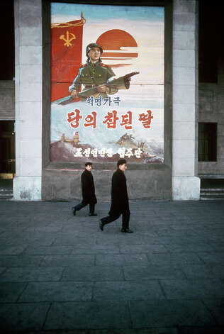Two men walking past a poster depicting North Korean revolutionary forces, North Korea, February 1973. Photo: John Bulmer, Getty Images / 2011 Getty Images