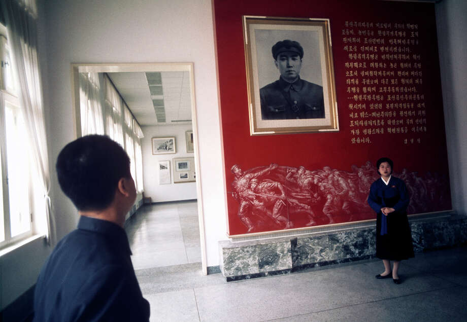 A visitor viewing a portrait of Communist leader Kim Il-sung at the Revolutionary Museum of Culture, Pyongyang, North Korea, February 1973. Photo: John Bulmer, Getty Images / 2011 Getty Images