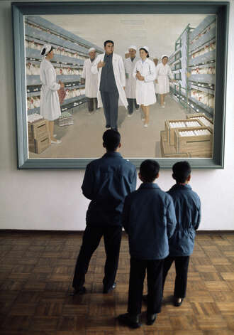 Three boys viewing a painting of North Korean Communist leader Kim Il-sung visiting a battery farm, North Korea, February 1973. Photo: John Bulmer, Getty Images / 2011 Getty Images