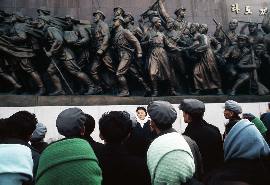 A guide (facing camera) with a group of visitors to the Mansudae Grand Monument, which depicts the North Korean revolutionary struggle, Pyongyang, North Korea, February 1973. Photo: John Bulmer, Getty Images / 2011 Getty Images