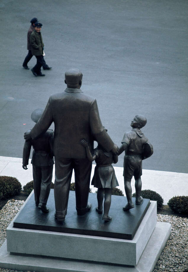 Two men walking past a statue of North Korean Communist leader Kim Il-sung with a group of children, North Korea, February 1973. Photo: John Bulmer, Getty Images / 2011 Getty Images