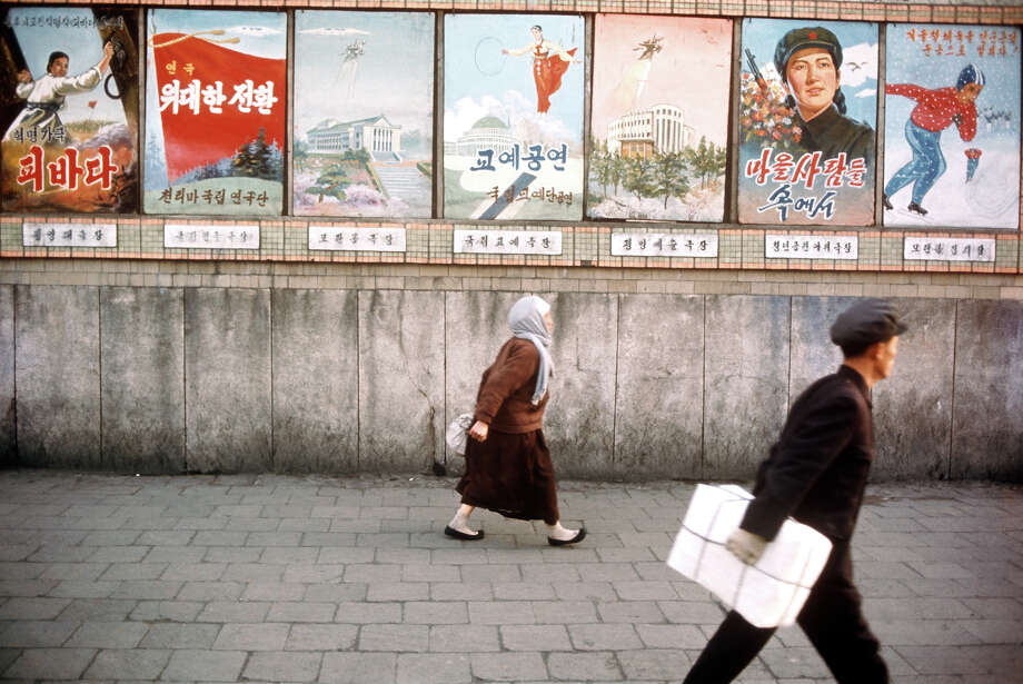 A man and a woman walking past a selection of posters, North Korea, February 1973. Photo: John Bulmer, Getty Images / 2011 Getty Images