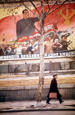 A man walking past a poster depicting Communist leader Kim Il-sung and North Korean revolutionary forces, North Korea, February 1973. Photo: John Bulmer, Getty Images / 2011 Getty Images