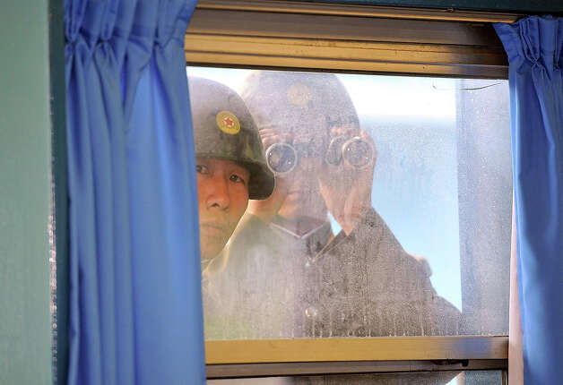 North Korean soldiers look in from outside the UN Command Military Armistice Commission meeting room as newly appointed commander General James Thurman (not in picture), commander of the United Nations Command (UNC), Combined Forces Command (CFC), and United States Forces Korea (USFK) visit to the border village of Panmunjom on July 15, 2011 in Panmunjom, South Korea. Thurman was appointed on Thursday as the commander of 28,500 American troops in South Korea in his capacity as commander of United States Forces Korea. Photo: Pool, Getty Images / 2011 Getty Images