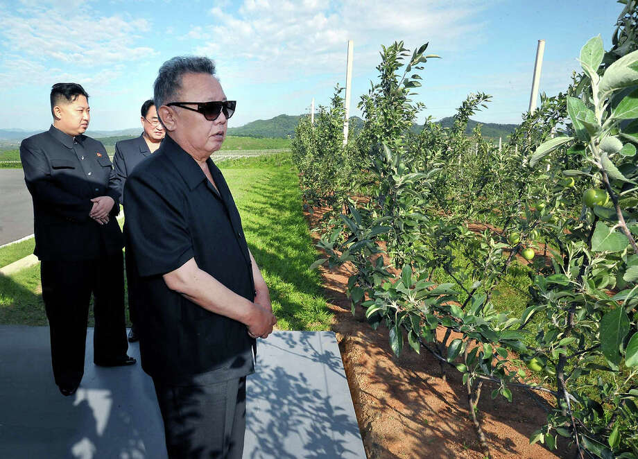 This undated picture released by North Korea's official Korean Central News Agency on July 23, 2011 shows North Korean leader Kim Jong-Il, right, and his son, Kim Jong-Un, left, visiting the Taedonggang Combined Fruit Farm and the newly built Taedonggang Combined Fruit Processing Factory at the suburb of Pyongyang. Photo: AFP, AFP/Getty Images / 2011 AFP