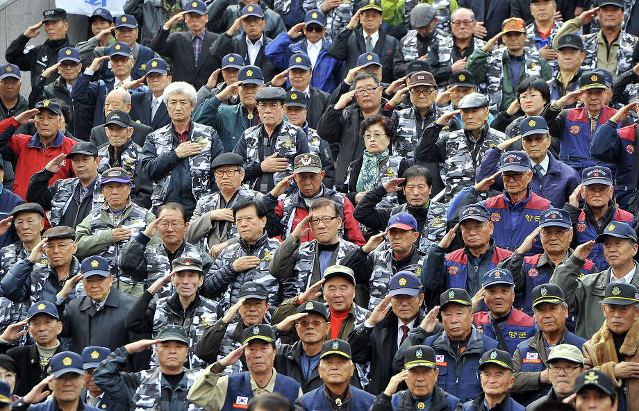 South Korean veterans and conservative activists salute the national flag during an anti-North Korea rally in Seoul on November 18, 2011, to mark the first anniversary of North Korea's artillery attack on the South Korean island of Yeonpyeong last November. South Korea's defense chief on November 18 pledged strong revenge for any provocations by North Korea in an order marking the anniversary of the attack on November 23. Photo: JUNG YEON-JE, AFP/Getty Images / 2011 AFP