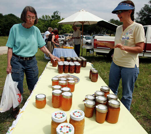 Dottie Watt, left, has a look at the preserves, jams and jellies offered by Martha Green, right, as Grey Forest held its first community farmers market, at the Scenic Loop Playground Club, Texas, Friday, May 19, 2007. Photo: J. MICHAEL SHORT, SPECIAL TO THE EXPRESS-NEWS / SAN ANTONIO EXPRESS-NEWS