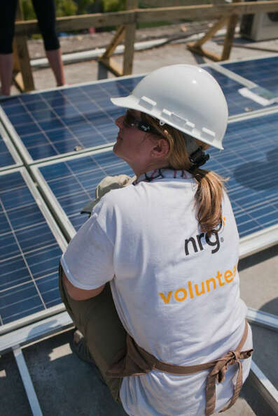 A woman with NRG Energy helps install a 100 kilowatt solar power system at Hospital Bernard Mevs in