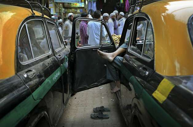 An Indian taxi driver waits for customers on a street in New Delhi, India, Thursday, March 14, 2013.  Photo: Kevin Frayer, Associated Press
