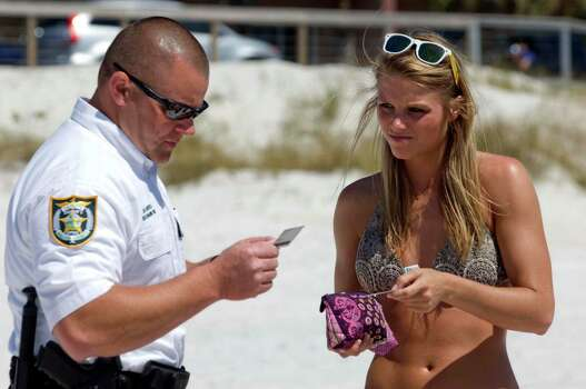Walton County Deputy Sheriff Brad Barefield, left, checks the IDs of Jenna Harris and other spring breakers from Mississippi on the beach in South Walton County, Florida on Wednesday, March 13, 2013.  As thousands of spring breakers descend on the beaches in this northwest Florida resort area, law enforcement personnel are making regular sweeps along the beaches looking for underage drinkers. Jenna Harris and the others in her party were over 21 years old and not ticketed. Photo: DEVON RAVINE, Associated Press / NORTHWEST FLORIDA DAILY NEWS
