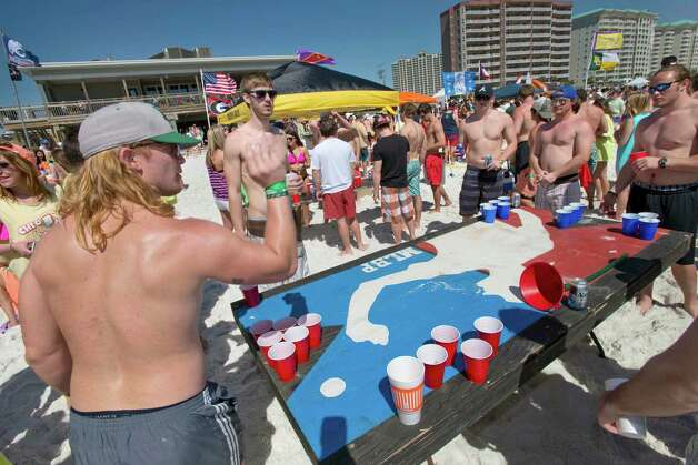 Rory Island, left, throws a ping-pong ball while playing beer pong with other spring breakers on the beach behind the Whale's Tail Restaurant in South Walton County, Florida on Wednesday, March 13, 2013. Photo: DEVON RAVINE, Associated Press / NORTHWEST FLORIDA DAILY NEWS