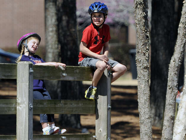 Emma Rasberry, 4, left, sings to herself while she and her brother Mason Rasberry, 9, enjoy the Spring Break weather near the Ag Pond on the campus of Stephen F. Austin State University on Wednesday, March 13, 2013, in Nacogdoches. Photo: Andrew D. Brosig, Associated Press / THE DAILY SENTINEL