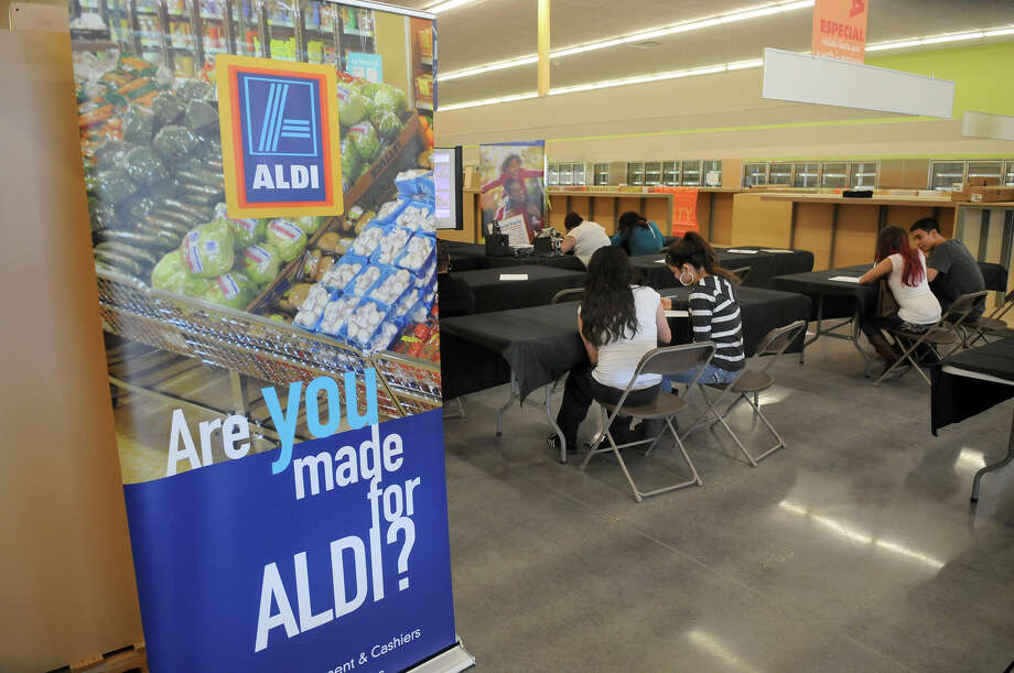 Job seekers fill out applications at Aldi's Humble store in 2013, when the grocer entered the local market.
