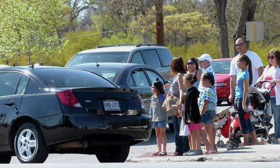 People wait to cross the intersection at Broadway and Mulberry on Wednesday, March 13, 2013. The presence of Brackenridge Park, Kitty Park and the Lions Field playground in the area, coupled with the rerouting of traffic that would normally travel on Hildebrand to Mulberry, have caused congestion. Photo: Billy Calzada, San Antonio Express-News / San Antonio Express-News