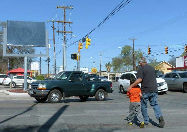 A man and child cross Mulberry at Broadway as a truck makes a turn in front of them on Wednesday, March 13, 2013. The presence of Brackenridge Park, Kitty Park and the Lions Field playground in the area, coupled with the rerouting of traffic that would normally travel on Hildebrand to Mulberry, have all caused congestion. Photo: Billy Calzada, San Antonio Express-News / San Antonio Express-News