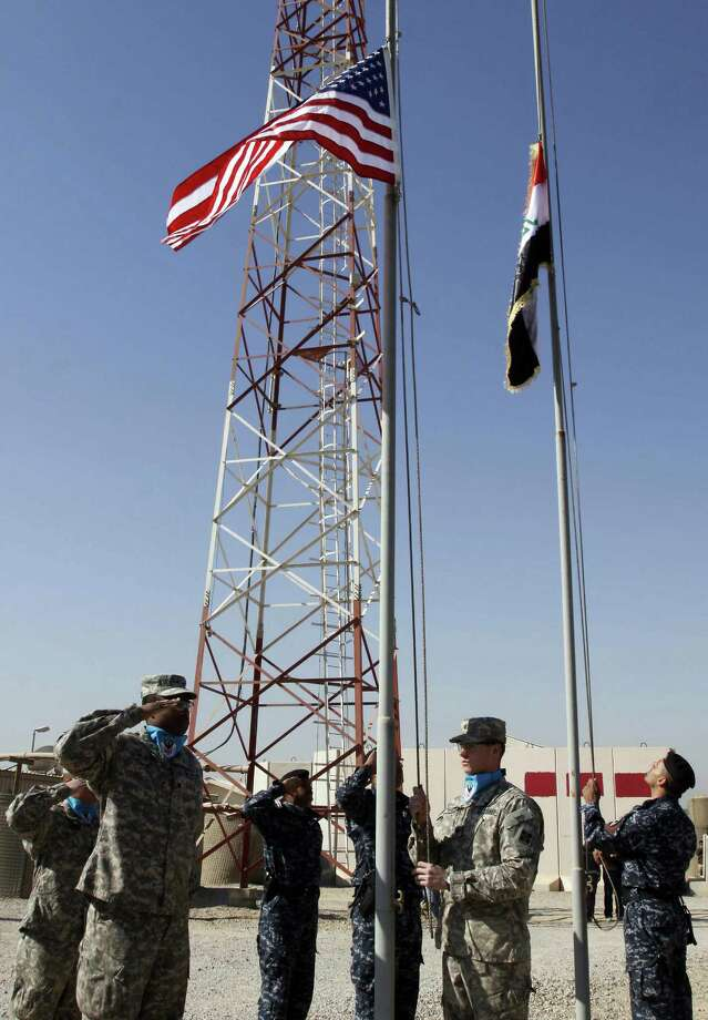 U.S. soldiers lower their national flag as Iraqi soldiers raise theirs during the handover ceremony of Bucca Camp in 2010. More than 4,000 U.S. soldiers and a million Iraqis died in the war. Photo: File Photo, AFP / Getty Images