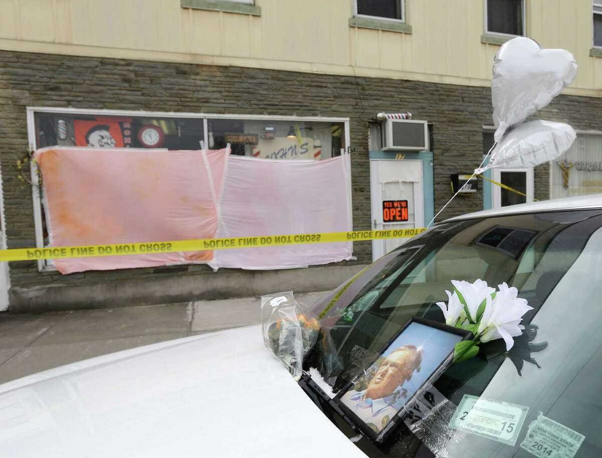 A memorial sits on a vehicle outside John's Barber Shop on, Thursday, March 14, 2013, in Mohawk, N.Y. Two customers were killed at the shop and two others were killed at a car wash in neighboring Herkimer on Wednesday. Authorities say the suspect in the shootings died in a shootout with police SWAT teams Thursday morning.